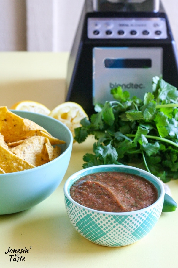 A bowl of salsa next to a bowl of chips and a blender