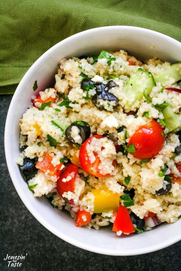 a close up of Greek couscous salad in a white bowl