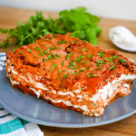 a slice of goat cheese lasagna on a blue plate with herbs in the background