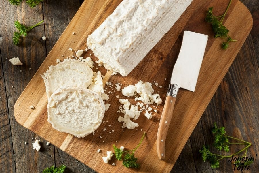 a log of goat cheese on a cutting board.  A couple slices sit next to a cleaver style knife and some crumbled goat cheese.