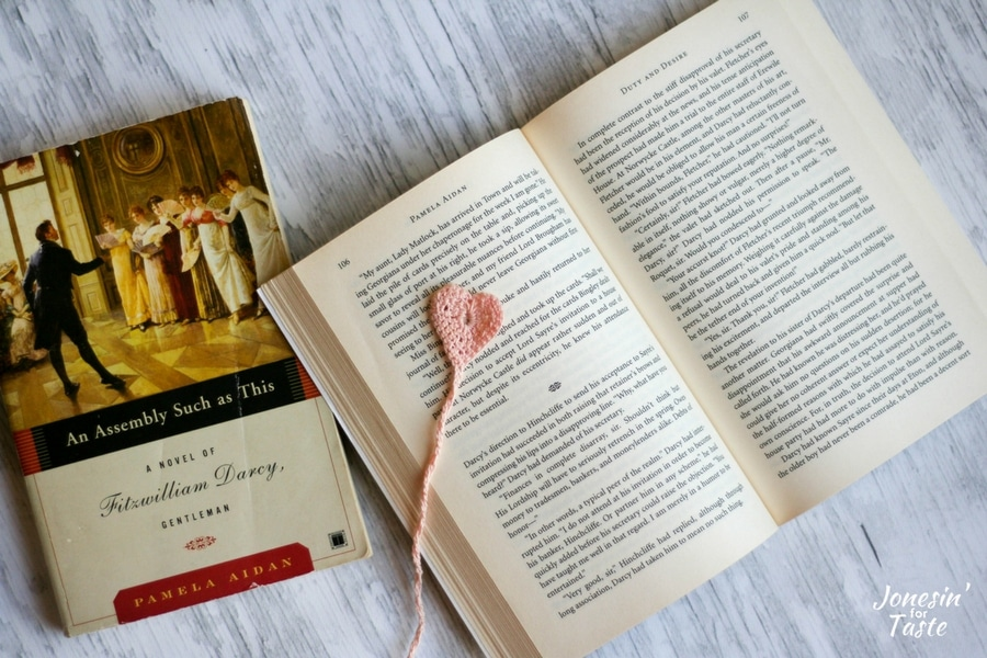 An open book with a crochet heart bookmark next to an additional closed book.