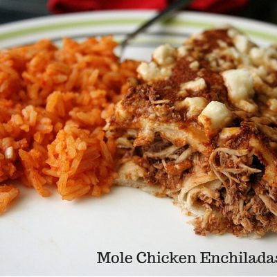 Two mole enchiladas cut in half on a plate next to Mexican rice