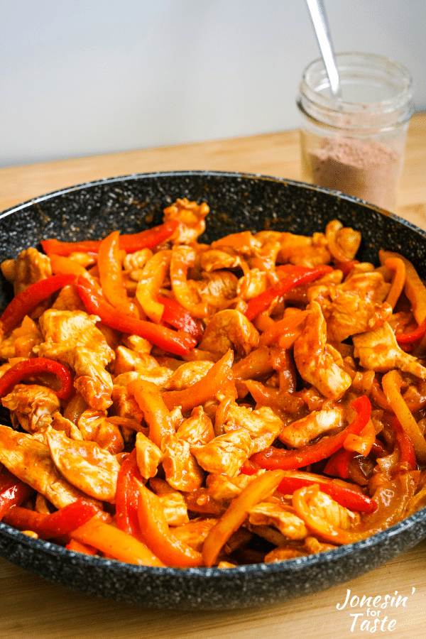 red tinged chicken fajitas in a black skillet