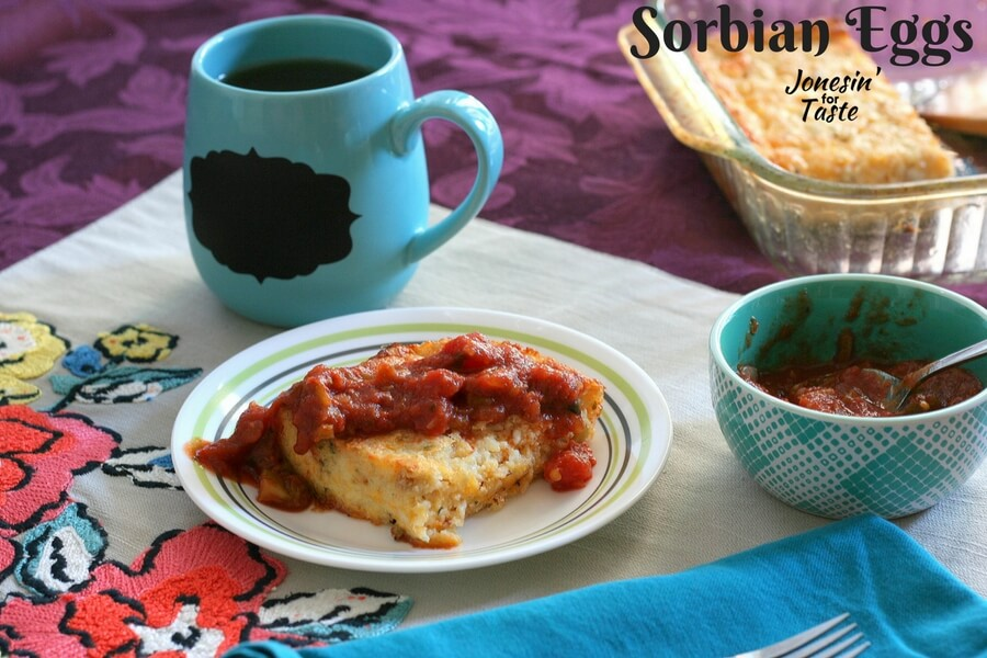 Sorbian Eggs on a table with a small blue bowl of salsa and the casserole dish in the background