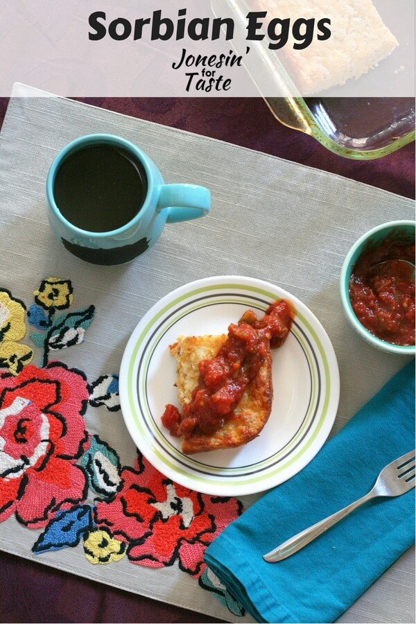 A slice of Sorbian Eggs topped with salsa on white plate on a bold flower placemat with a blue mug.