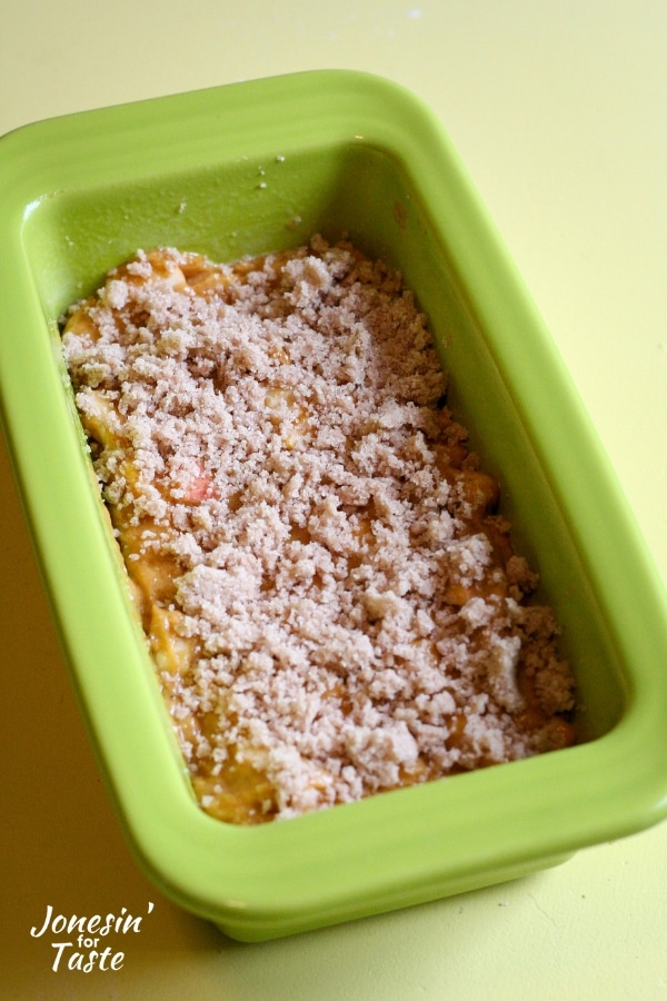 A loaf pan with bread batter sprinkled with streusel topping