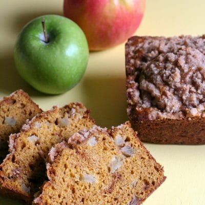 Slices of pumpkin apple bread next to a loaf and apples