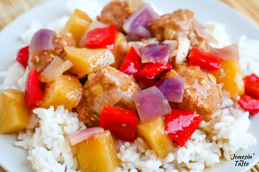 meatballs with chunks of peppers, onions, and pineapple over rice