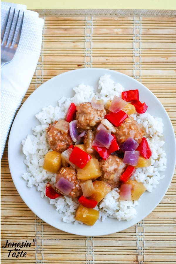 A plate of sweet and sour meatballs on a bamboo place mat