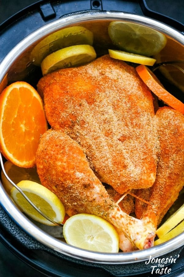 a whole chicken coated in a spice rub sits in a pressure cooker pot surrounded by orange and lemon slices