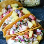 Fish tacos and grilled corn on a black cutting board
