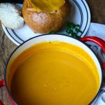 A red pot with pumpkin soup