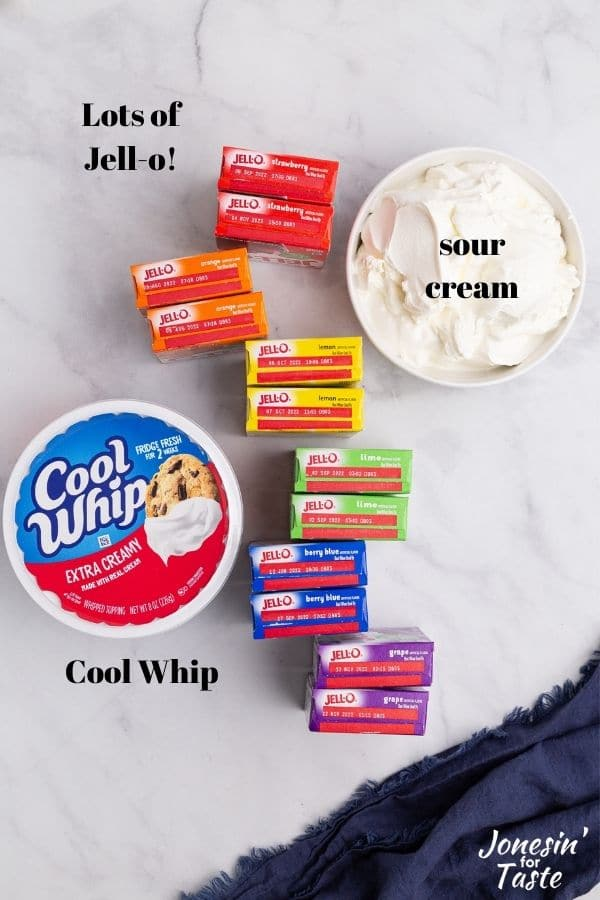 a bowl of sour cream, boxes of jello, and a tub of cool whip on a white counter