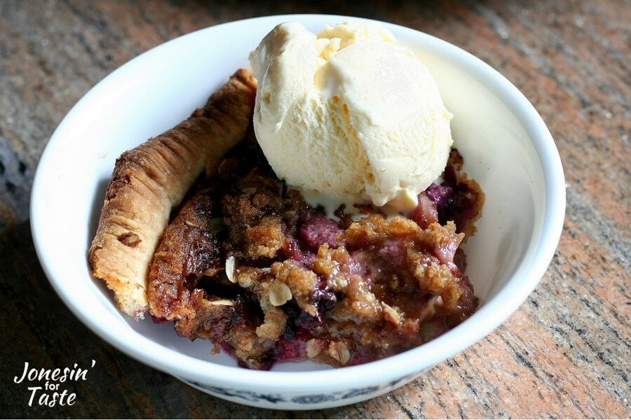 A slice of apple crumble pie topped with a scoop of vanilla ice cream in a white bowl
