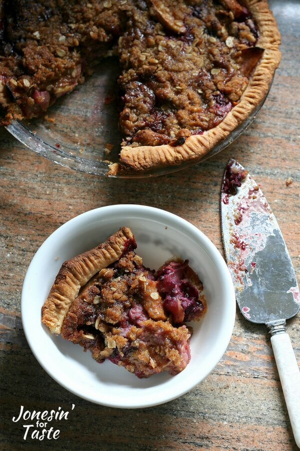 A slice of apple berry pie in a bowl sitting next to the whole pie with a pie server next to both.