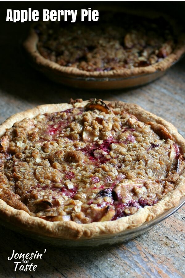 Two apple berry pies topped with oatmeal crumble and with purple and blue berries peaking out of the oatmeal crumble.