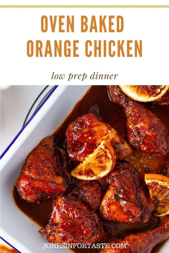 a rich dark brown sauce coats chicken pieces in a white casserole dish garnished with halved orange slices