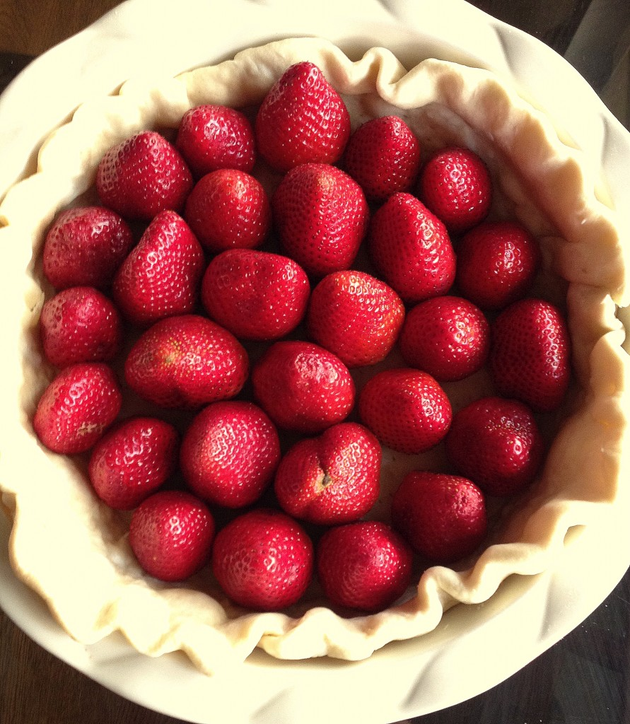 Whole strawberries sitting in a cooked pie crust for No Bake Fresh Strawberry Pie