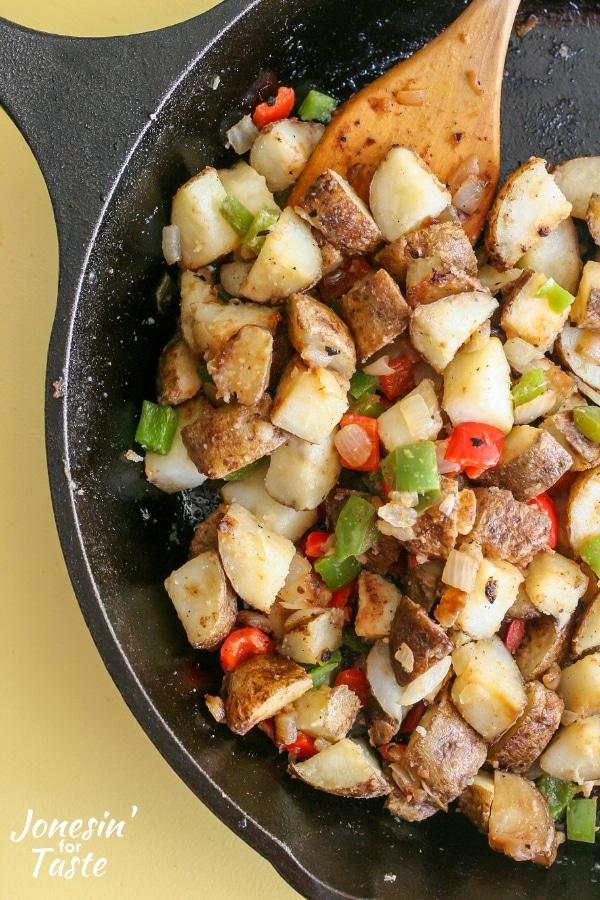 A spatula stirring potatoes o brien