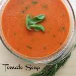 a glass bowl of tomato soup with 3 Basil leaves in the center