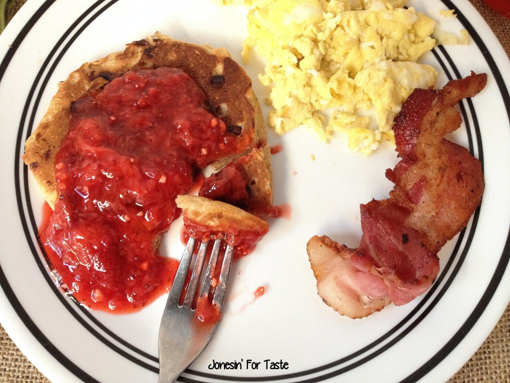 pancakes topped with strawberry sauce with scrambled eggs and bacon