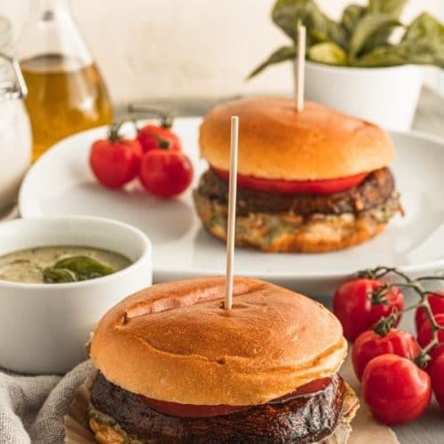 a Portobello burger sits on torn piece of parchment paper in front of a Portobello burger on a plate with various bowls of pesto and basil and tomatoes on the vine around them