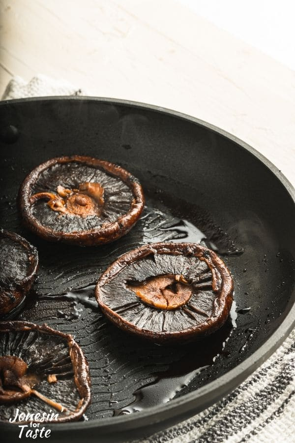 Cooked Portobello mushrooms sit cap side down in a black skillet