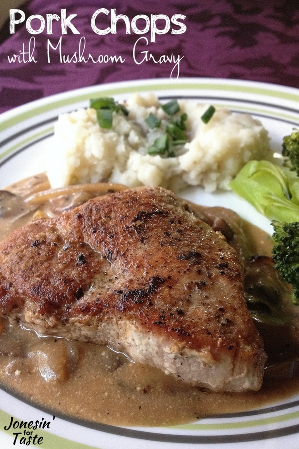 A purple tablecloth with a white plate filled with mashed potatoes topped with green onions, broccoli spears, and pork chops with mushroom gravy