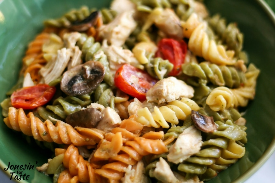 Tri-color pasta with pesto chicken, tomatoes, and mushrooms all tossed with alfredo sauce.