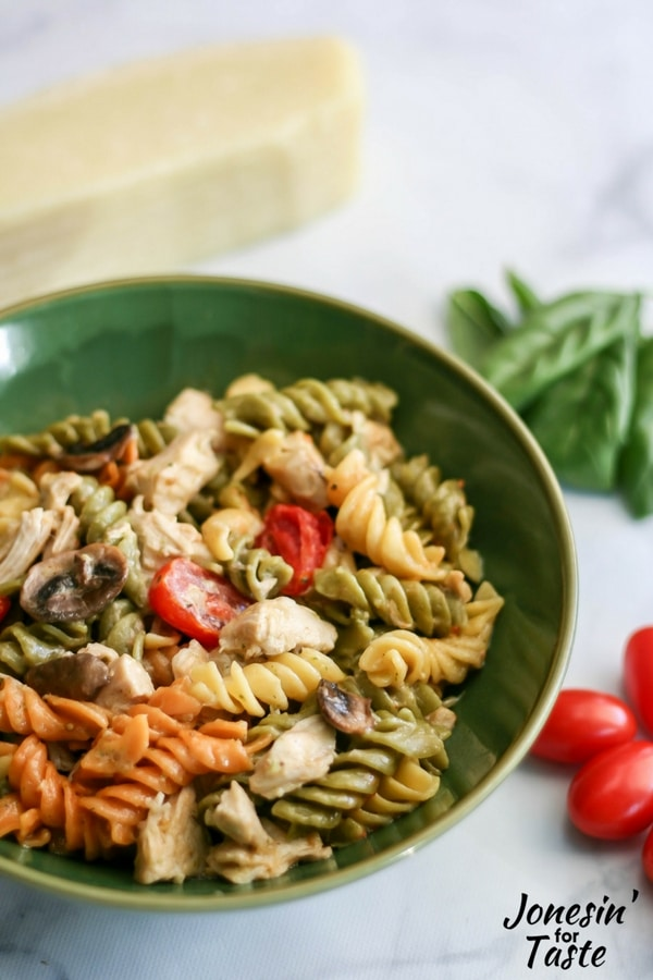 A green bowl filled with pesto chicken alfredo surrounded by groups of basil leaves, cherry tomatoes, and a hunk of parmesan cheese.