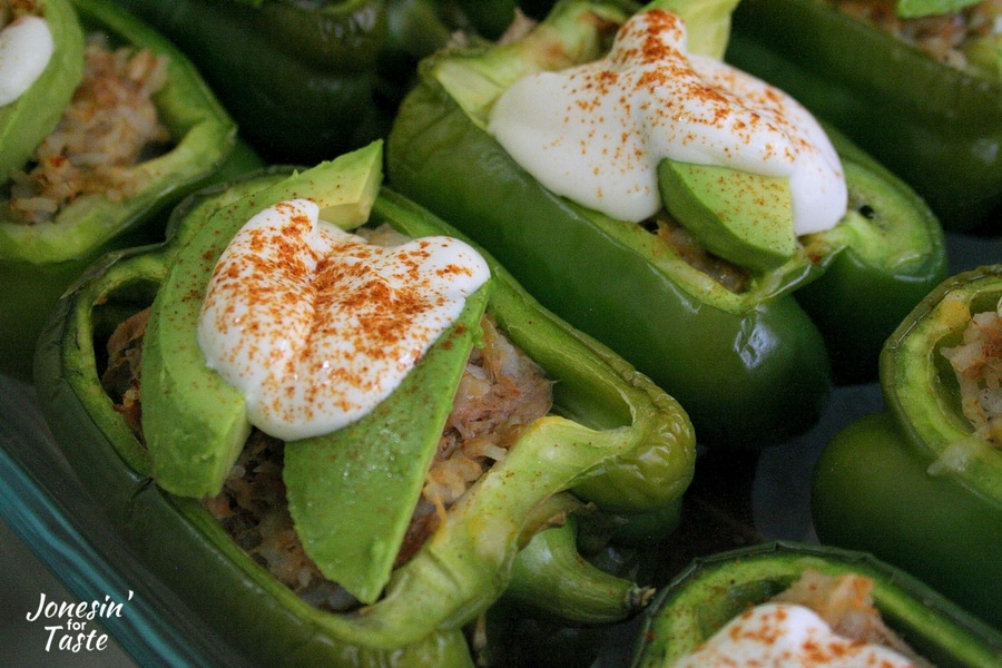 A pair of Southwest Stuffed peppers topped with avocados and lime yogurt sauce