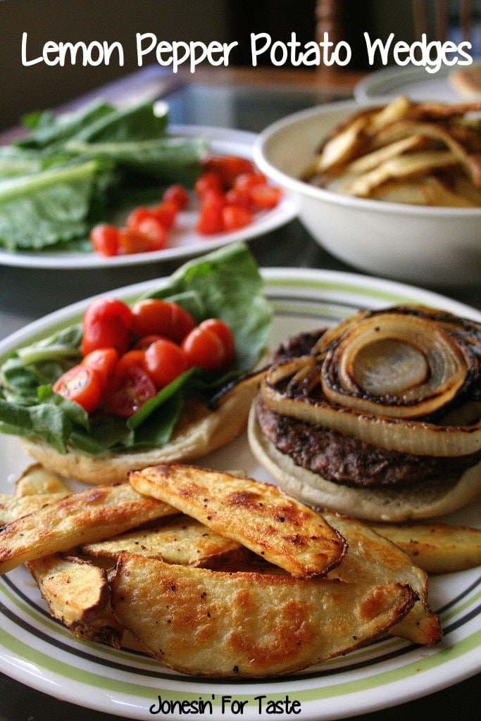 A plate with slices of Lemon Pepper Potato Wedges with a hamburger and a bowl of potato wedges in the background along with a plate of hamburger toppings.