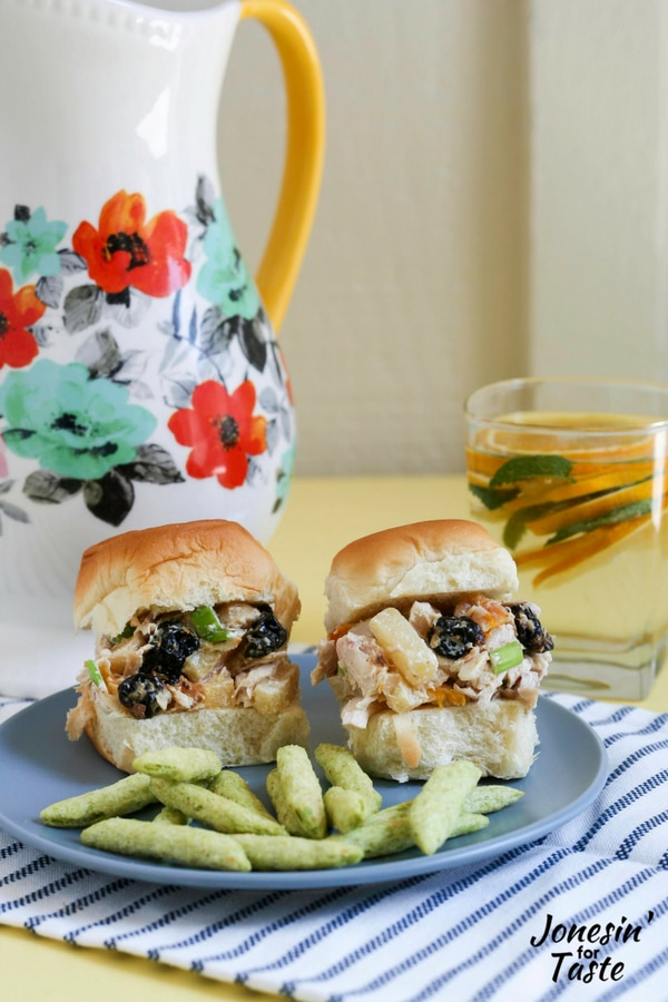 Tropical Chicken Salad sandwiches, snap pea crisps, and mint citrus water on a table.