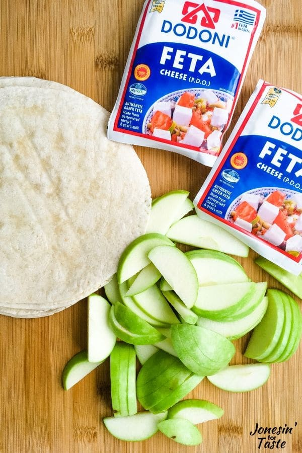 tortillas, sliced apples and feta cheese packages on a cutting board