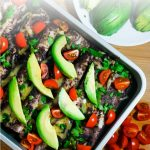 a pan of enfrijoladas topped with avocados, cilantro, and sliced tomatoes