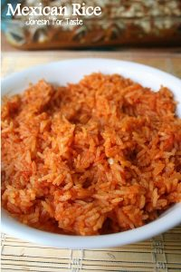 A bowl of Mexican rice sitting in front of a casserole dish