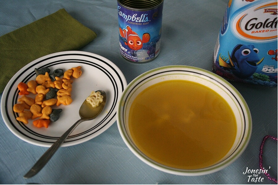 A bowl of soup and Goldfish crackers on a plate