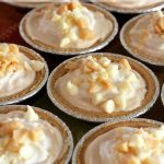 A bunch of mini no bake pumpkin cheesecakes grouped together tightly on a table.
