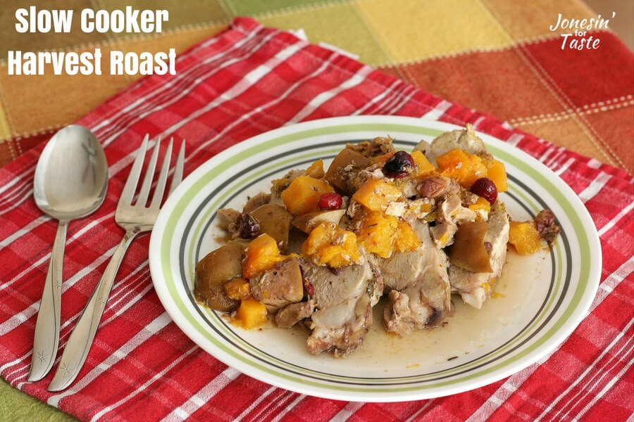 A plate of slow cooker harvest roast sliced and served up with the cooked squash, apples, and cranberries.