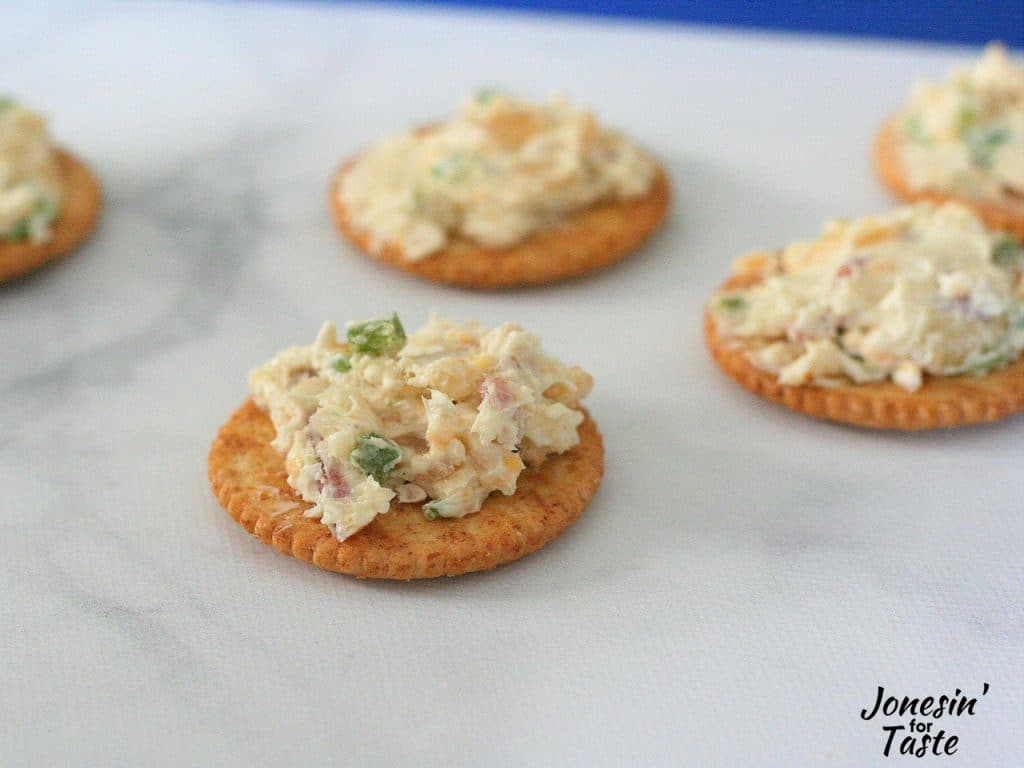 Bacon and Jalapeno cheese log spread on ritz crackers on a marble surface.
