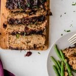 cranberry turkey meatloaf laid out on a wooden cutting board. Slices are falling over and everything is sprinkled with fresh herbs.