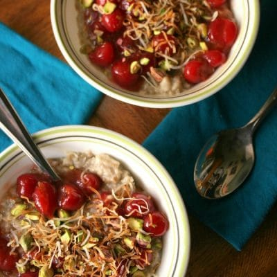 Looking down on two bowls of Slow Cooker Cherry Coconut Steel Cut Oatmeal with blue napkins on a wooden table.