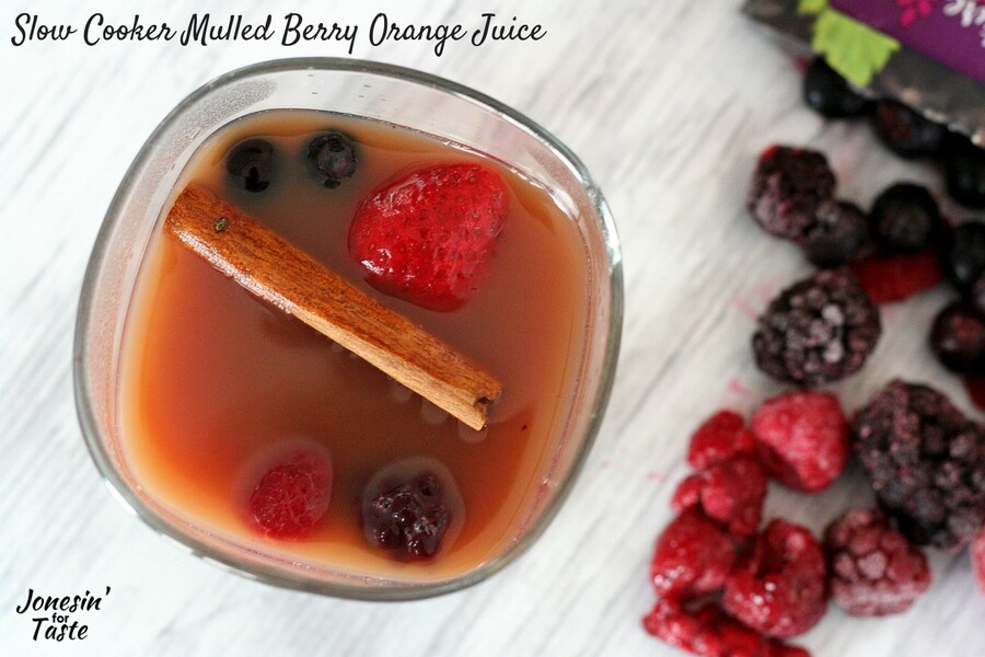 Slow Cooker Mulled Berry Orange Juice viewed from above with a cinnamon stick and extra berries in the glass.