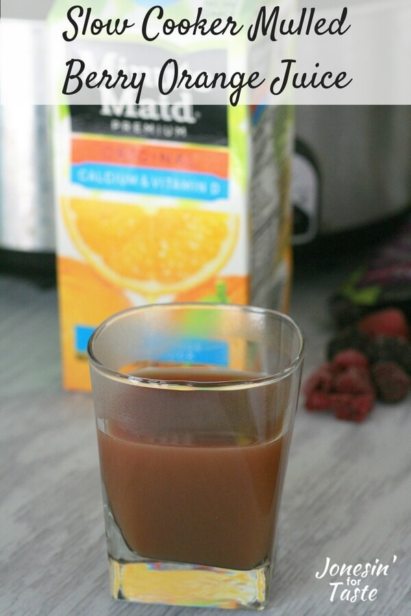 Simple Slow Cooker Mulled Berry Orange Juice in a glass cup in front of a container of orange juice