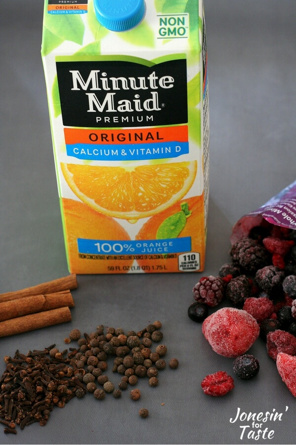 Showing the ingredients for Slow Cooker Mulled Berry Orange Juice including frozen berries, spices, and orange juice.