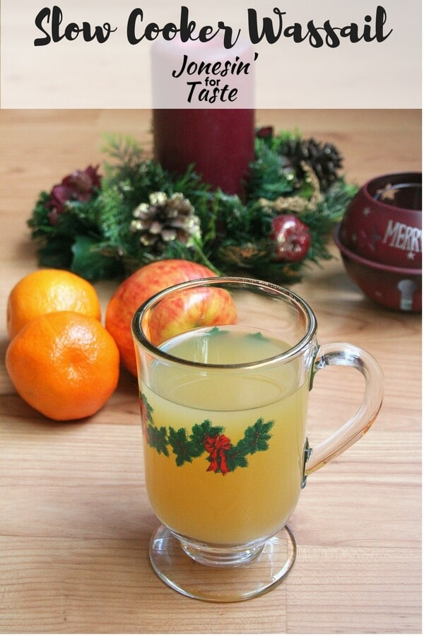 Easy Slow Cooker Wassail in a glass mug with oranges and apples and Christmas decor in the background