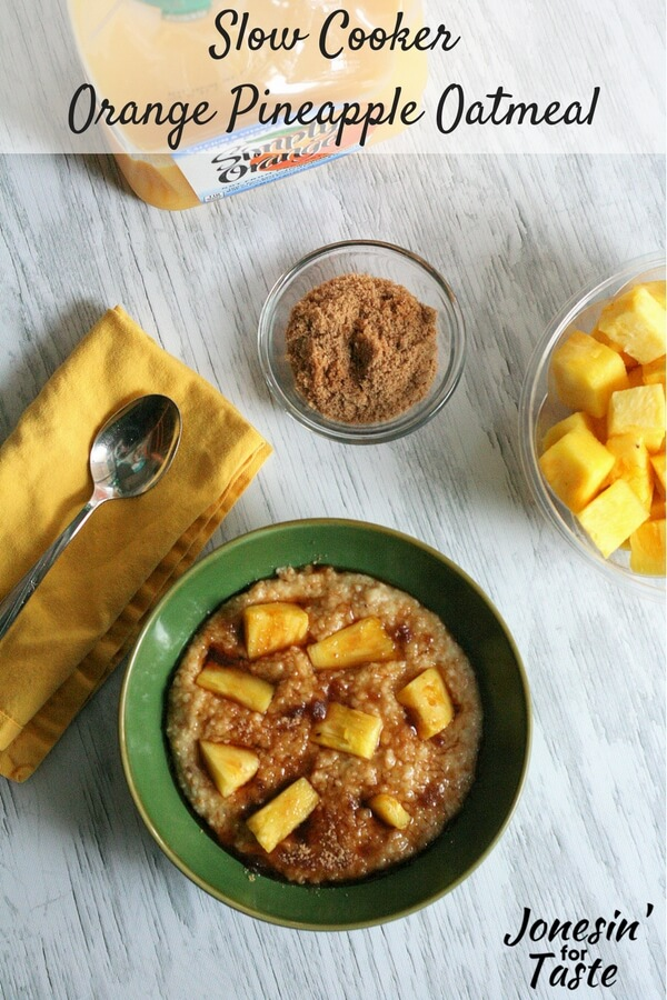 A green bowl of Slow Cooker Orange Pineapple Oatmeal on a white table with sides of fresh pineapple and a small bowl of brown sugar.