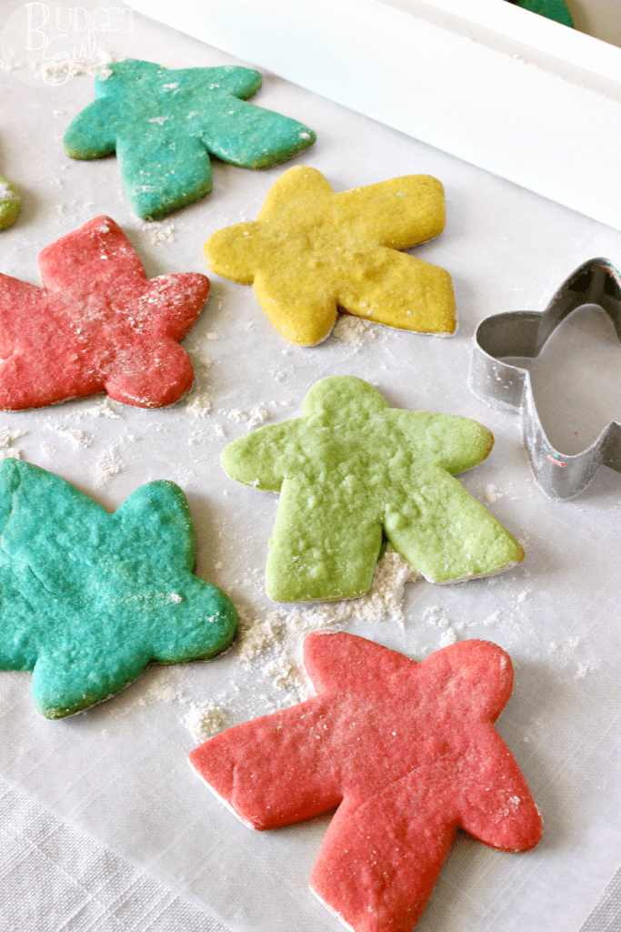 Sugar cookie cutouts of Meeples in red, yellow, green, and blue