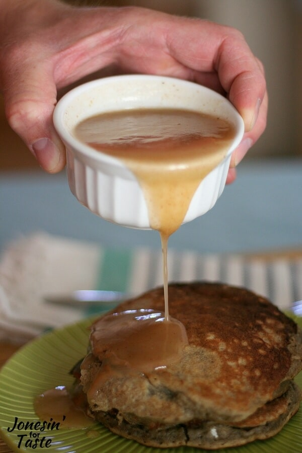 Apple syrup being poured over a stack of pancakes.
