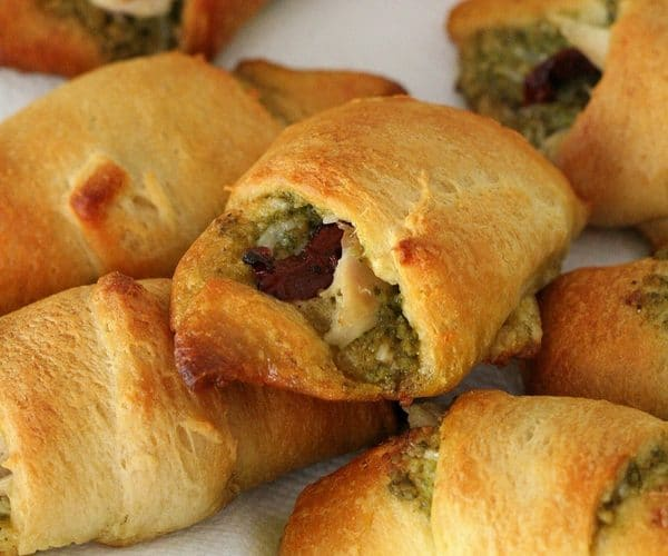 A pile of chicken croissants with pesto and sun dried tomato